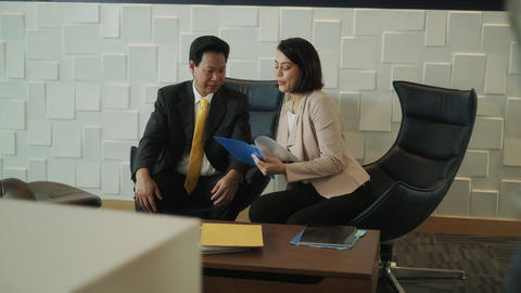 Investment Plan Agent Showing Documents To Asian Customer In Bank Footage
