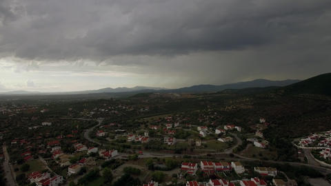 Drone flying and descending over town, view to cottages and green spaces, Greece Live Action
