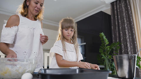 Young mother and little daughter making cookies in kitchen. Woman and little Footage