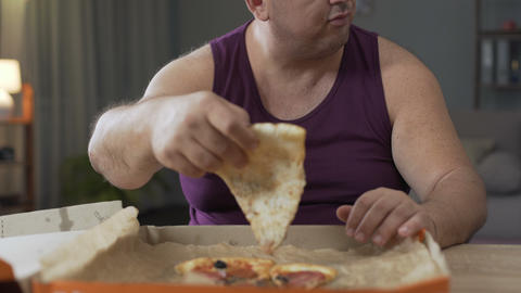 Overweight male eating pizza quickly at night time, addiction to unhealthy food Live Action
