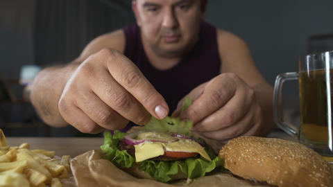 Man decorating high-calorie burger with salad leaf, preparing to eat, obesity Footage