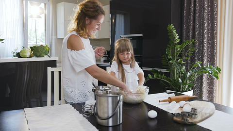 Ride the camera. A young woman and little daughter are baking in kitchen. Young Footage