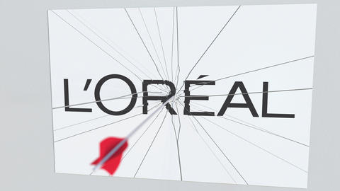 LOREAL company logo being hit by archery arrow. Business crisis conceptual Live Action