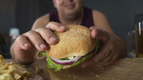 Obese man taking big burger but not biting it, refusal from bad eating habits Live Action