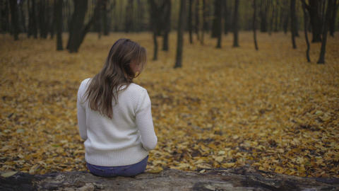 Girl sitting in autumn park alone, thinking about past and broken relationship Footage