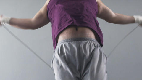 Chubby man jumping rope, taking care of health and body shape, slow-motion Footage