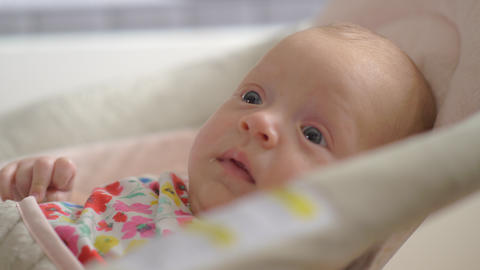 Quiet blue-eyed baby girl of two months in bouncy seat at home Footage