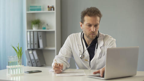 Doctor viewing test results on laptop and writing down medical records, medicine Footage