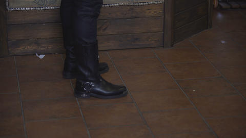 Cool macho in blue jeans walking into pub, meeting friend at bar counter, bikers Footage