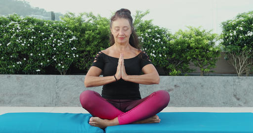 mature woman doing lotus yoga position outside in the garden ビデオ