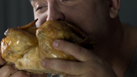Bad mannered guy biting into fried chicken, food addiction leading to illnesses Footage