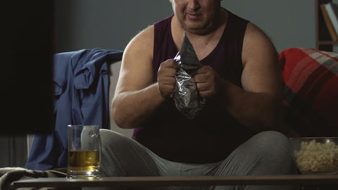 Big guy tearing a pack of potato chips apart, messy lifestyle, unhealthy food Live Action