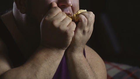 Messy overweight man stuffing with greasy hamburger, psychology of overeating Live Action