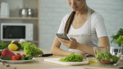 Attractive female sitting at the table and reading salad recipe on cellphone Footage