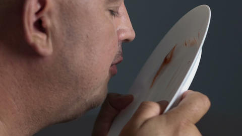 Obese guy eating remains of ketchup and mayo from plate, junk and greasy food Live Action
