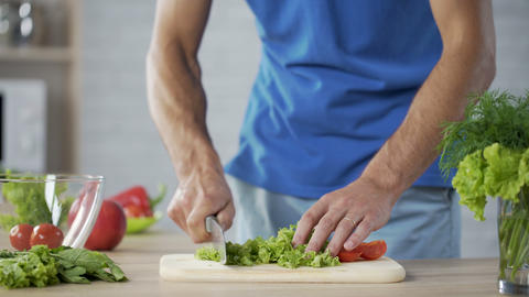 Male preparing vegetable salad carefully controlling his health and nutrition Live Action