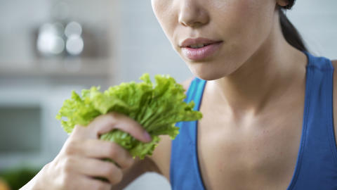 Wishing lose weight and be slim, lady making herself eating lettuce, nutrition Live Action