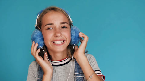Lovely smiling girl is wearing big blue headphones listening to music inside of Footage