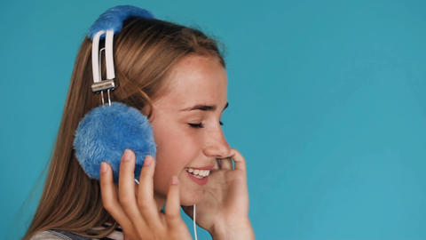 Lovely smiling girl is wearing big blue headphones... Stock Video Footage