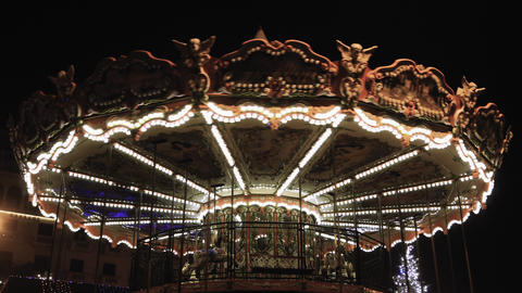 Illuminated vintage fairground carousel with wooden horses rotating at night Footage