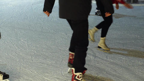 People ice skating on evening ice-rink in winter city ビデオ