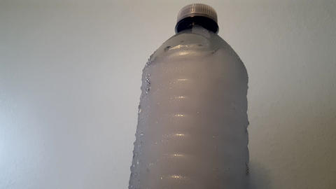 Water Beads off Ice Water Bottle as it Melts Up-Close Footage