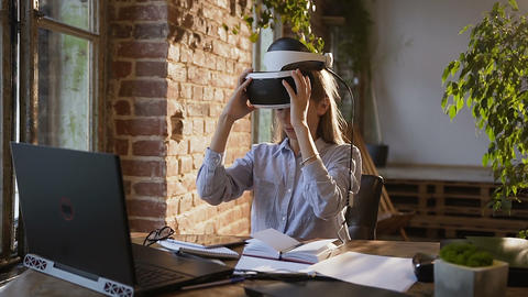 Young creative girl uses virtual reality glasses at workplace in modern office Footage