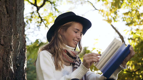 Portrait shot of smiling girl with beautiful scarf reading book in the city park Live Action