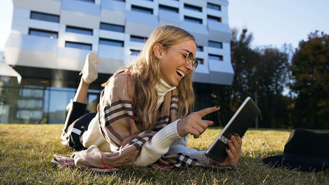 Portrait shot of cute young woman typing message to the friends in her tablet Live Action