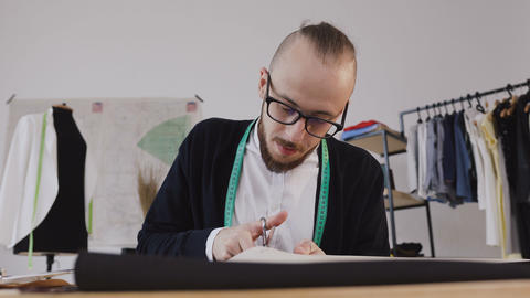 Close-up of a young beared designer or tailor in eyeglasses who sitting at a Footage