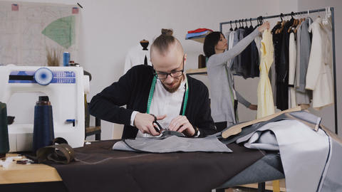 Tailor or fashion designer sits on the workplace at studio and cutting fabric Footage