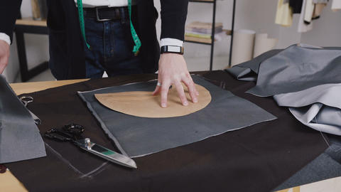 Handsome tailor working in his studio, drawing template on fabric. Creative a Footage