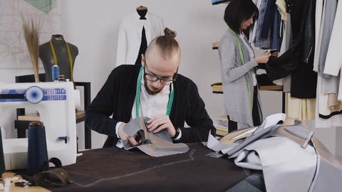Bearded tailor or fashion designer sits on the workplace at studio and cutting Footage