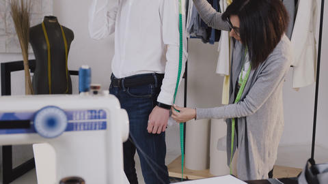 Young professional dressmaker taking measurements for sewing suit at tailors Footage