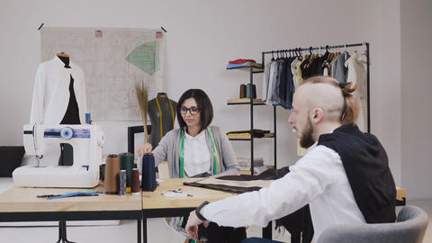 Two people fashion designers choosing fabric at the office with different Footage