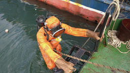 Frogman in orange equipment for diving climbs ladder out of water on boat Footage