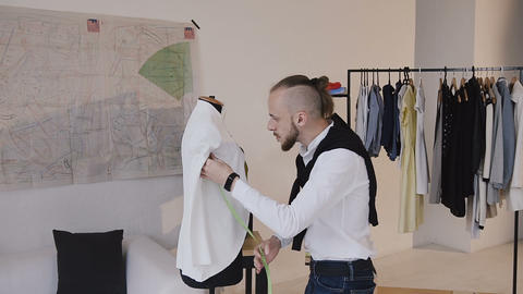 Tailor working and dancing at work, measures the long sleeve white jacket using Footage