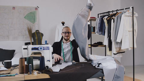 Creative designer and tailor is sitting at the desk in his design studio and Footage