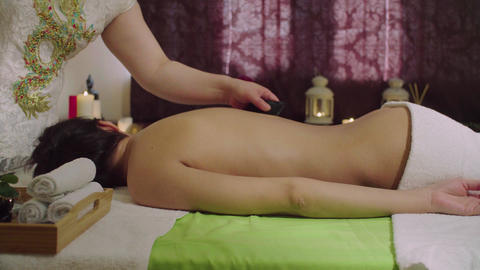 Chinese doctor doing stone massage to a young woman Footage