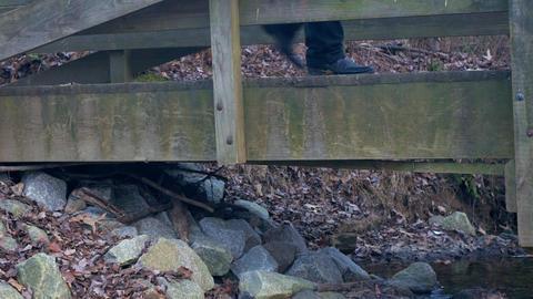 foot traffic walking past camera on a small wooden bridge Footage