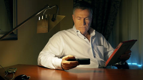 businessman working at his desk with a tablet pc and phone Footage