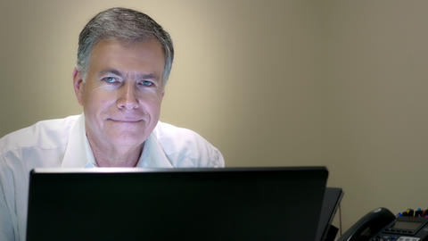 businessman working at his desk smiles at camera 4k Footage