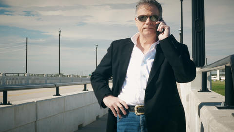 businessman talking on his cellphone at the side of a bridge 4k Live Action