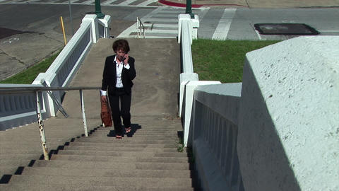 businesswoman walking up an outside set of stairs Live Action