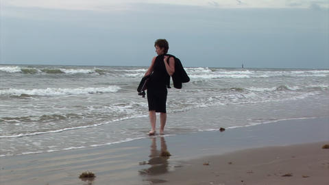 Businesswoman Walking Along An Ocean Beach stock footage