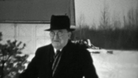 1937: Jolly old man slipping on ice winter cold weather almost falls Footage