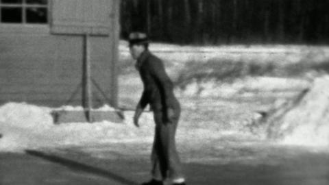 1937: Man ice skating backwards winter flooded backyard rink Footage