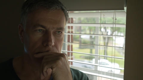 man thinking of something serious and looks out window 4k Live Action