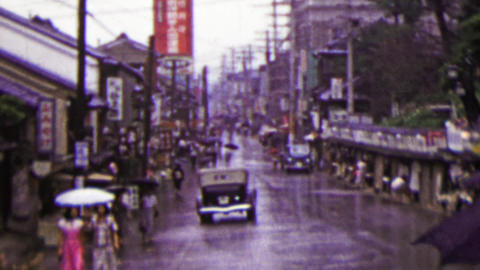 1951: Busy Japanese commercial street raining umbrellas drawn Footage