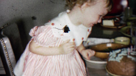 1956: Toddler girl blowing out birthday cake candles proud parents watch Footage